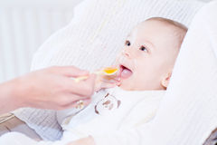 Bébé garçon de alimentation de mère avec la cuillère de bébé Image stock