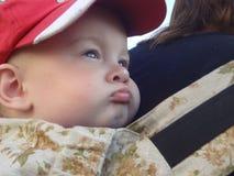 Bébé garçon de bandit avec des lèvres et des joues sur le mother& x27 ; s de retour a froncé les sourcils Photos stock