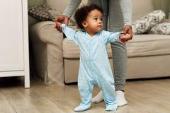 Bébé garçon de enseignement de mère à marcher dans une chambre image libre de droits