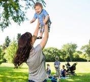 Bébé garçon de levage de mère espiègle en parc Image libre de droits