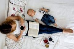 Bébé garçon de mère et d'enfant en bas âge, se situant dans le lit, étreignant avec amour, salut Photographie stock libre de droits