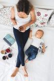 Bébé garçon de mère et d'enfant en bas âge, se situant dans le lit, étreignant avec amour, salut Photos libres de droits