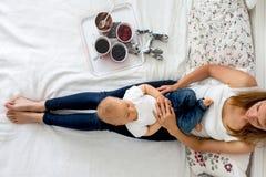 Bébé garçon de mère et d'enfant en bas âge, se situant dans le lit, étreignant avec amour, salut Images libres de droits