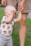Bébé garçon de premières étapes avec la mère en parc Autour de beaucoup d'herbe verte et arbres pendant l'été Image libre de droits