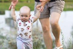 Bébé garçon de premières étapes avec la mère en parc Autour de beaucoup d'herbe verte et arbres pendant l'été Photographie stock libre de droits