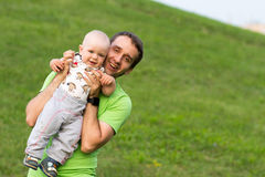 Bébé garçon de premières étapes avec le père en parc Autour de beaucoup d'herbe verte et arbres pendant l'été Image stock