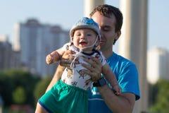 Bébé garçon de premières étapes avec le père en parc Autour de beaucoup d'herbe verte et arbres pendant l'été Images libres de droits