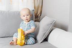 bébé garçon de six mois pleurant tandis que la mère change sa couche image stock