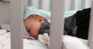 Bébé garçon de sommeil mignon dans la huche banque de vidéos