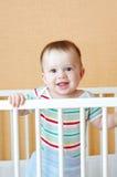 Bébé garçon de sourire dans le lit blanc Photographie stock
