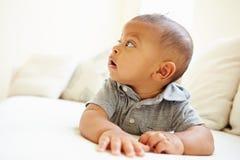 Bébé garçon de sourire se trouvant sur le ventre à la maison Image stock