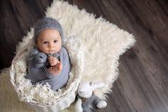 Bébé garçon doux dans le panier, tenant et étreignant l'ours de nounours, lookin Photo libre de droits