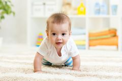 Bébé garçon drôle de rampement à l'intérieur à la maison images stock