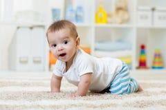 Bébé garçon drôle de rampement dans la crèche à la maison images stock