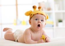 Bébé garçon drôle dans le chapeau de girafe se trouvant sur son ventre dans la crèche Peu d'enfant se trouve sur le lit avec la b Images libres de droits