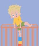 Bébé garçon essayant de s'élever hors du parc Photo stock