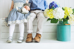 Bébé garçon et fille s'asseyant sur un plancher en bois Photos stock