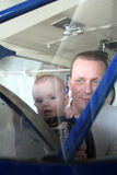 Bébé garçon et homme souriant dans le pare-brise de l'avion antique Image libre de droits