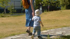 Bébé garçon et sa maman marchant en parc banque de vidéos
