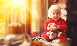 Bébé garçon heureux avec l'ours de nounours au sujet de la fenêtre d'automne Photographie stock libre de droits