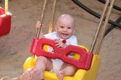 Bébé garçon heureux dans l'oscillation Image stock
