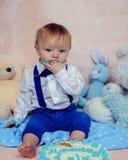 Bébé garçon heureux mangeant le gâteau pour sa première fête d'anniversaire Image stock