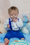 Bébé garçon heureux mangeant le gâteau pour sa première fête d'anniversaire Photos stock