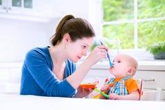 Bébé garçon heureux mangeant son premier witn solide de nourriture sa mère Image stock