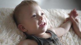 Bébé garçon heureux souriant et jouer le mensonge sur le lit banque de vidéos