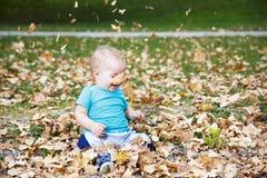 Bébé garçon jouant avec des feuilles en automne Photographie stock