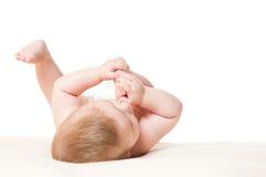 Bébé garçon jouant avec ses pieds Images stock