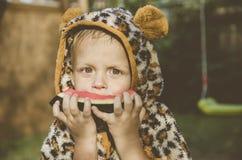Bébé garçon jouant dans le jardin Le garçon mangeant la pastèque Photographie stock libre de droits