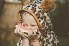 Bébé garçon jouant dans le jardin Le garçon mangeant la pastèque Photo stock