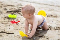 Bébé garçon jouant sur la plage sablonneuse Images libres de droits