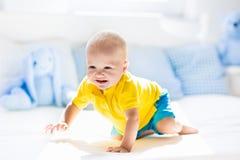 Bébé garçon jouant sur le lit dans la crèche ensoleillée Photographie stock libre de droits