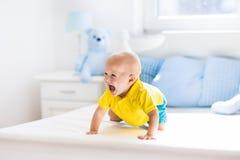Bébé garçon jouant sur le lit dans la crèche ensoleillée Photographie stock