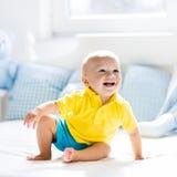 Bébé garçon jouant sur le lit dans la crèche ensoleillée Image libre de droits