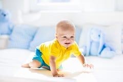 Bébé garçon jouant sur le lit dans la crèche ensoleillée Photo libre de droits