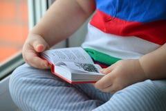 Bébé garçon lisant un livre, dclose des mains poussant des feuilles par les pages image libre de droits