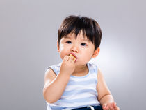 Bébé garçon mangeant le biscuit Photo libre de droits