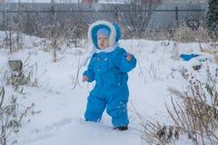 Bébé garçon marchant à une cour de neige Photos stock