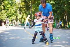 Bébé garçon mignon avec l'instructeur de patinage intégré dans le learini de parc Images libres de droits