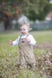 Bébé garçon mignon courant par des feuilles d'automne photographie stock