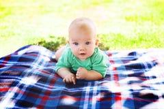 Bébé garçon mignon d'enfant se trouvant sur la couverture dans le jour d'été sur la nature Images libres de droits