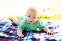 Bébé garçon mignon d'enfant se trouvant sur la couverture dans le jour d'été sur la nature Photographie stock