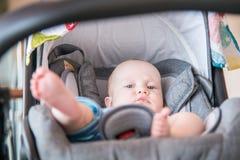 Bébé garçon mignon dans sa poussette se couchant, se reposant Image stock
