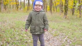 Bébé garçon mignon dans une course de veste verte parmi les feuilles tombées en parc d'automne Fin vers le haut banque de vidéos