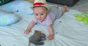 Bébé garçon mignon de bébé de 5 mois avec son Straw Hat On un tapis de jeu banque de vidéos