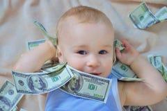Bébé garçon mignon jouant avec l'argent, argent liquide de dollars US Images libres de droits