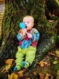Bébé garçon mignon jouant avec un jouet en bois de hochet et s'asseyant par t Photo libre de droits